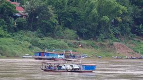 Local ferry boats carry people across Mekong river. Luang prabang, Laos - AUGUST 7, 2015: Local ferry boats carry people and other vehicles across Mekong river stock footage