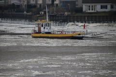 Local ferry between Gouderak and Moordrecht between the ice flak. Es on river Hollandse IJssel in Netherlands Royalty Free Stock Images