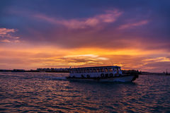 Local ferry swimming near Male town, Maldives at sunset. Local ferry swimming near Male town, at sunset Royalty Free Stock Photography