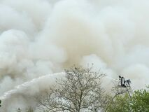 Firefighters up in bucket spraying a stream of water on an unseen fire, the background filled with white smoke