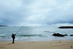 local fisherman angler casting his lure at a sandy shore beach on the atlantic ocean royalty free stock photos