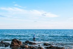 Local fisherman is fishing with fishing rod in evening at Nui be Royalty Free Stock Photos