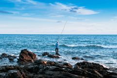 Local fisherman is fishing with fishing rod in evening at Nui be Royalty Free Stock Photo
