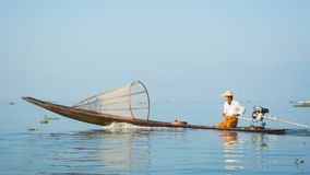 Local fisherman floats on fishing boat with a motor. Inle lake, Burma (Myanmar) stock video footage