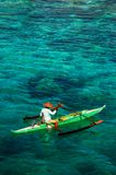 Amazing colours of the water in the Philippines. A local fisherman gets out on the water at the crack of dawn to start his daily work stock image