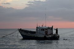 South Jamaica Travel. Local fisherman are seen on a boat from the shore at dusk in Treasure Beach, Jamaica Stock Photos