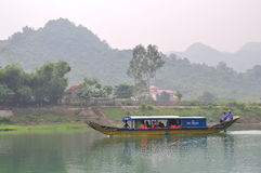 Local fisherman is taking tourists to travel on a traditional small boat Royalty Free Stock Photo