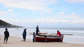 Local fishermen attending to their small fishing boat on fish hoek beach Cape Town
