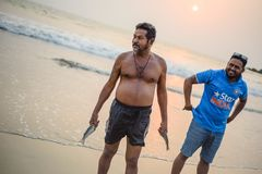 Local fishermen collecting their catch from sea. India, Goa, March 29 2017: Local fishermen collecting their catch from sea on the beach in Arambol at sunset Royalty Free Stock Image