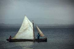 Local fishermen sail a small boat Stock Images