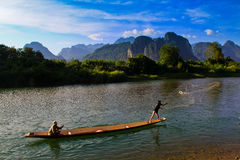 Local fishermen in Vang Vieng, Laos. Vang Vieng, Laos, December 2012. In an amazing scenery, local fishermen try to catch some fish in Nam Song River. This river Stock Photo