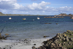 Local fishing boats anchored off rocky shore Stock Photos