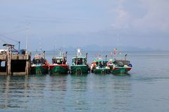Local fishing boats parked together on the pier stock image