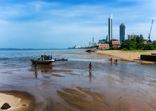 Local fishing workers prepare boat at low tide. Stock Image