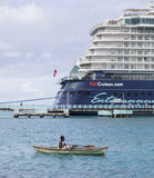 Local fishingboat versus cruise ship. A small local Jamaican fishingboat is passing a giant cruise ship Stock Images
