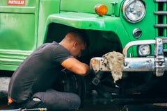 A local fixing his truck in Havana city, Cuba. A local fixing his bright green taxi truck in Havana city, Cuba stock photo
