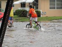 Local Flood - Boys Biking Through Water Royalty Free Stock Images