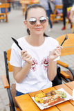 The local food festival. A beautiful girl eats fried sausages and vegetables Royalty Free Stock Photography