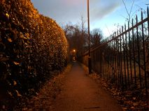 Footpath at dusk. A local footpath in Southern England, dimly lit with the remains of the day`s sun and the warm glow of old sodium street lamps Royalty Free Stock Image