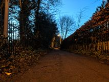 Footpath at dusk. A local footpath in Southern England, dimly lit with the remains of the day`s sun and the warm glow of old sodium street lamps Stock Images