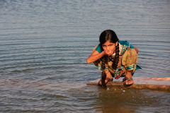 Local girl drinking from water reservoir, Khichan village, India Royalty Free Stock Images