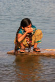 Local girl drinking from water reservoir, Khichan village, India Royalty Free Stock Photos