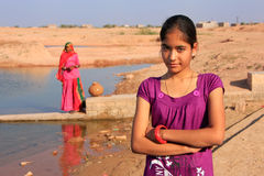 Local girl standing near water reservoir, Khichan village, India Royalty Free Stock Photo