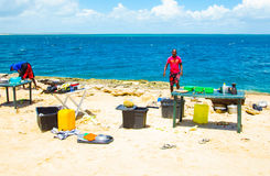 Local guides cooking with sandy ocean background in Mozambique. Tour to the sandy Bazaruto island in Bazaruto Archipelago with local people.Mozambique, Africa Royalty Free Stock Image