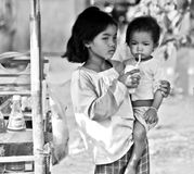 Khmer Girl with baby sister. Local Khmer girl hanging out with sister, drinking in Sisophon, Western Cambodia Royalty Free Stock Images