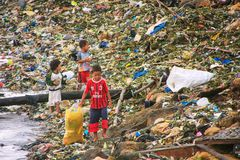 Local kids going through garbage at the sea coast in Labuan Bajo town, Flores Island, Indonesia stock image