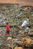 Local kids going through garbage at the sea coast in Labuan Bajo town, Flores Island, Indonesia royalty free stock images