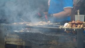 Local lady is cooking the local barbecues stock footage