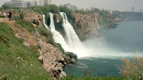 A local landmark, a beautiful waterfall on a cliff. Tourists go upstairs and look at the beautiful view.  stock footage
