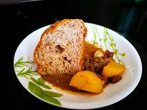 Kuzi Daging sweet meat curry being served with a wholemeal bread in a plate on black background. stock photos