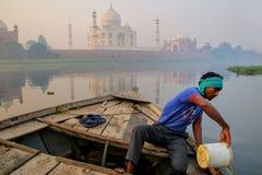 Local man bailing water out of the boat on Yamuna River near Taj Mahal in the morning, Agra, Uttar Pradesh, India