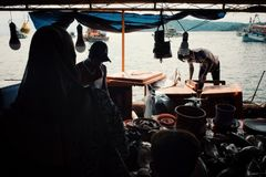 Local man cleaning fish at the fishing market next to the shore royalty free stock images