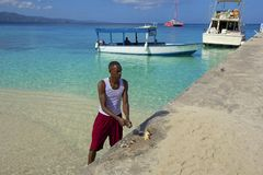 Local man cutting fish in Doctor's Cove Beach in Jamaica, Caribbean Royalty Free Stock Photo