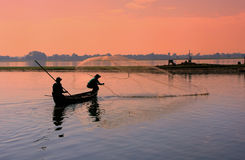 Local man fishing with a net from a boat, Amarapura, Myanmar Stock Photos