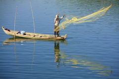 Local man fishing with a net from a boat, Amarapura, Myanmar Royalty Free Stock Photo