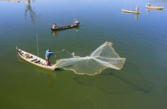 Local man fishing with a net from a boat, Amarapura, Myanmar Stock Images