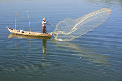 Local man fishing with a net from a boat, Amarapura, Myanmar Royalty Free Stock Images