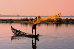 Local man fishing with a net at sunset, Amarapura, Myanmar Stock Image
