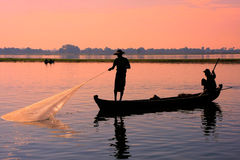 Local man fishing with a net at sunset, Amarapura, Myanmar Stock Photo