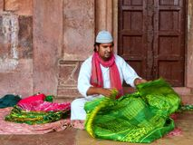 Local man folding cloth inside Jama Masjid in Fatehpur Sikri, Ut. Tar Pradesh, India. The mosque was built in 1648 by Emperor Shah Jahan and dedicated to his Stock Images