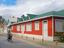 Local man on a motorbike riding along colorful buildings Royalty Free Stock Photos