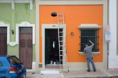 A local man painting window in old San Juan. San Juan, Puerto Rico, USA - Jan. 2, 2018: A local man painting the window of a traditional house in the streets of royalty free stock photography