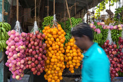 Local man passing by street fruit stand Stock Images