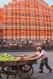 Local man pushing cart in front of Hawa Mahal in Jaipur, Rajasthan, India stock photo