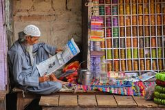 Local man reading newspaper at the street market in Fatehpur Sik. Ri, Uttar Pradesh, India. The city was founded in 1569 by the Mughal Emperor Akbar, and served Stock Photos