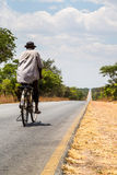 Local man riding on a bike on a desolated road Royalty Free Stock Photo